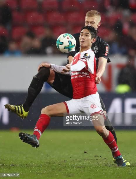 Yoshinori Muto of Mainz is challenged by Timo Baumgartl of Stuttgart during the Bundesliga match between 1 FSV Mainz 05 and VfB Stuttgart at Opel...