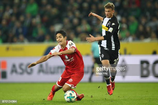 Yoshinori Muto of Mainz runs for the ball with Mickael Cuisance of Moenchengladbach during the Bundesliga match between Borussia Moenchengladbach and...