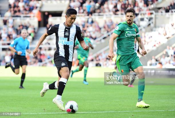 Yoshinori Muto of Newcastle United battles for possession with Craig Cathcart of Watford during the Premier League match between Newcastle United and...