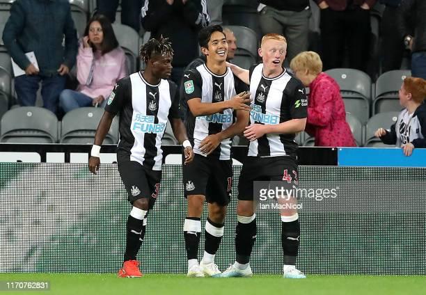 Yoshinori Muto of Newcastle United celebrates after scoring his team's first goal with Matthew Longstaff of Newcastle United and Christian Atsu of...