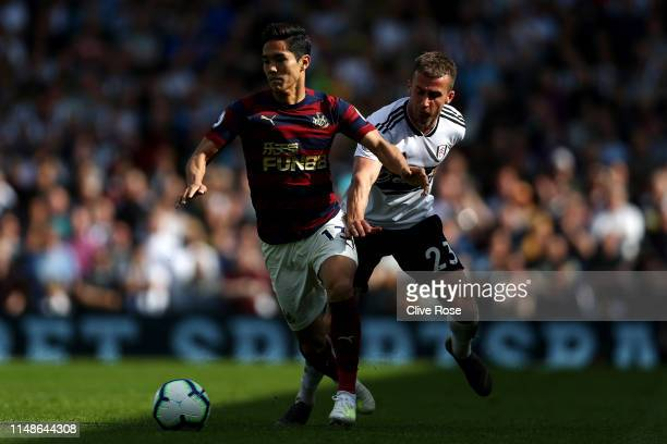 Yoshinori Muto of Newcastle United evades Joe Bryan of Fulham during the Premier League match between Fulham FC and Newcastle United at Craven...