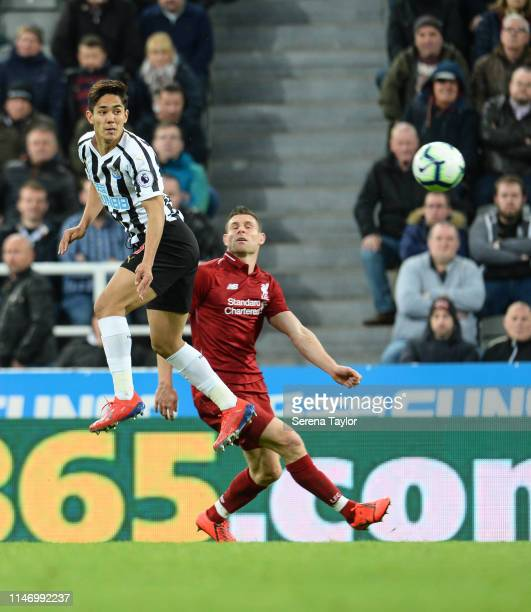 Yoshinori Muto of Newcastle United heads the ball past James Milner of Liverpool during the Premier League match between Newcastle United and...