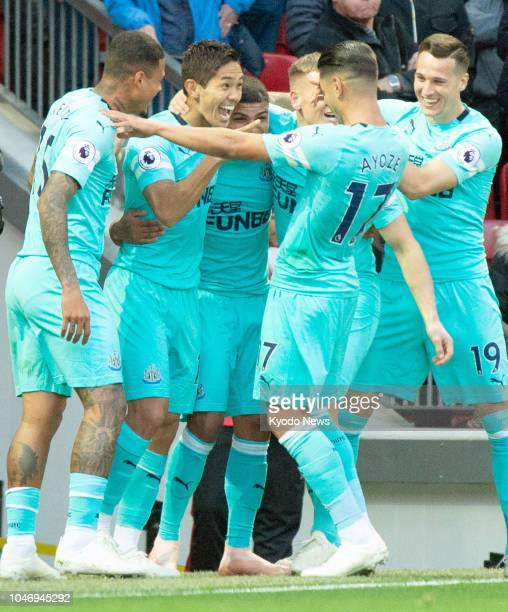 Yoshinori Muto of Newcastle United is congratulated by his teammates after scoring his team's second goal during the first half of a Premier League...