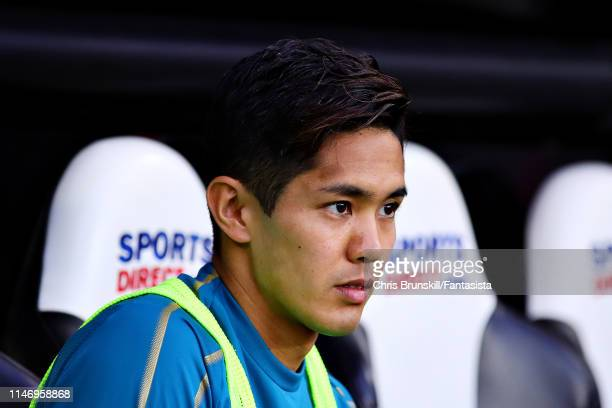 Yoshinori Muto of Newcastle United looks on from the substitutes bench during the Premier League match between Newcastle United and Liverpool FC at...