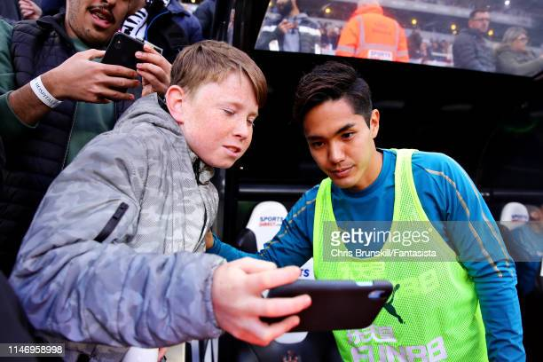 Yoshinori Muto of Newcastle United poses for a photo with a fan on the substitutes bench before the Premier League match between Newcastle United and...