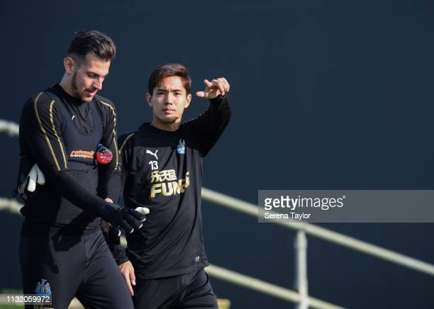 Yoshinori Muto points to the camera whilst walking outside with Goalkeeper Martin Dubravka during the Newcastle United Training Session at the...