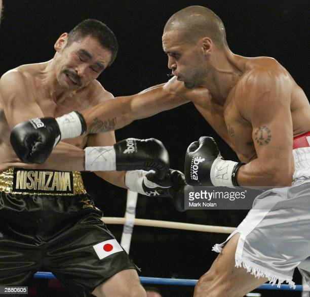 Yoshinori Nishizawa grimaces as Anthony Mundine throws a punch during the WBA Super Middle Weight Boxing Title Defence between the current champion...