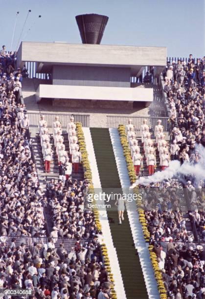 Yoshinori Sakai goes up steps in the national stadium to light torch signifying opening of games