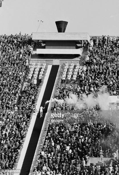 Yoshinori Sakai of Japan climbs the stairway to light the Olympic flame during the opening ceremony at the National Stadium for the XVIII Summer...