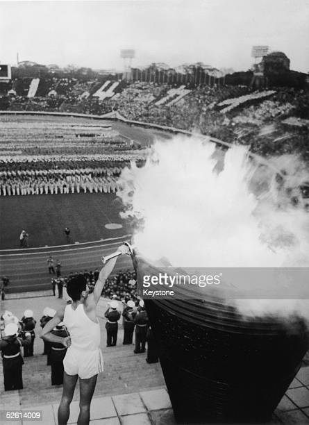 Yoshinori Sakai who was born in Hiroshima on the day the first atomic bomb devastated the city lights the Olympic flame in Tokyo's main stadium...