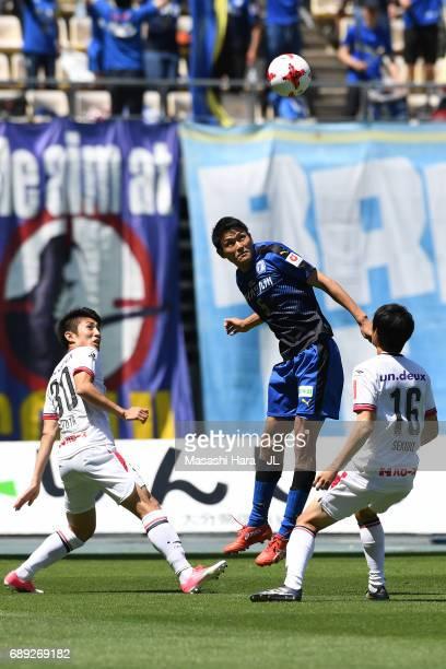 Yoshinori Suzuki of Oita Trinita heads the ball in front of Yuta Toyokawa and Kenji Sekido of Fagiano Okayama during the JLeague J2 match between...