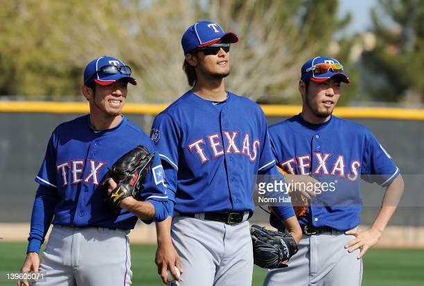 Yoshinori Tateyama Yu Darvish and Koji Uehara of the Texas Rangers get ready to throw from the mound during spring workouts at Surprise Stadium on...