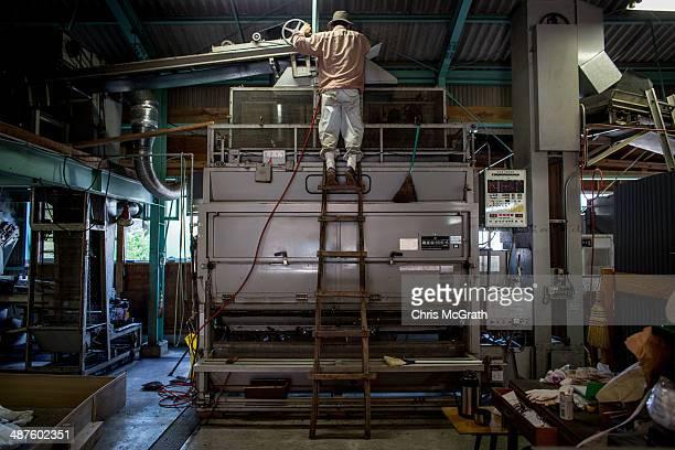 Yoshio Moriuchi checks a machine used to dry freshly picked tea leaves at his farm on May 1, 2014 in Shizuoka, Japan. Japan produces aproximately...