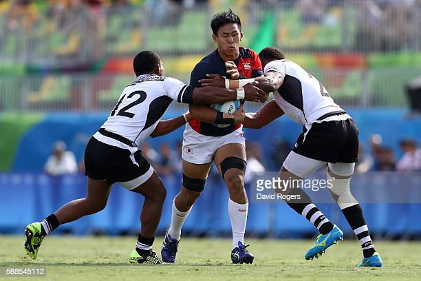 Yoshitaka Tokunaga of Japan is tackled by Vatemo Ravouvou and Jasa Veremalua of Fiji during the Men's Rugby Sevens semi final match between Fiji and...