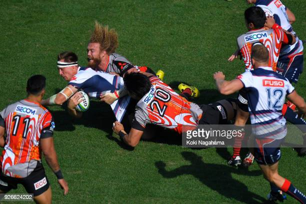 Yoshitaka Tokunaga of Sunwolves and Willem Britz of Sunwolves make a tackle on Jack Maddocks of Rebels during the Super Rugby round 3 match between...