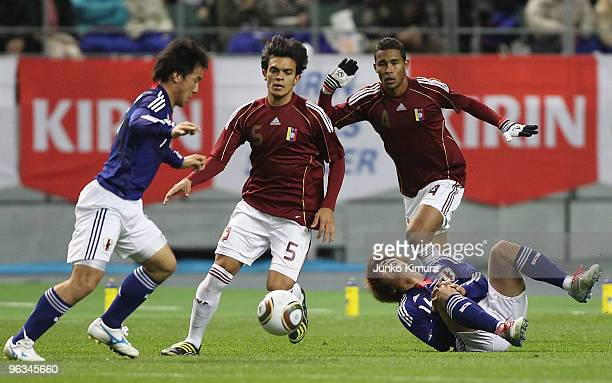 Yoshito Okubo of Japan and Giacomo Di Giorgi of Venezuela fight for the ball during Kirin Challenge Cup Soccer match between Japan and Venezuela at...