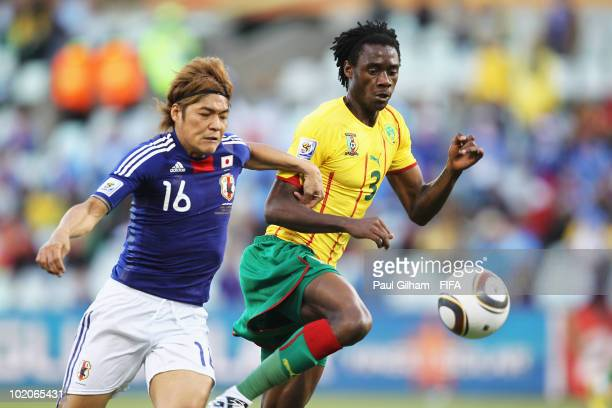 Yoshito Okubo of Japan and Nicolas Nkoulou of Cameroon run for the ball during the 2010 FIFA World Cup South Africa Group E match between Japan and...