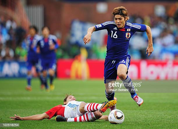Yoshito Okubo of Japan in action against Enrique Vera of Paraguay during the 2010 FIFA World Cup South Africa Round of Sixteen match between Paraguay...