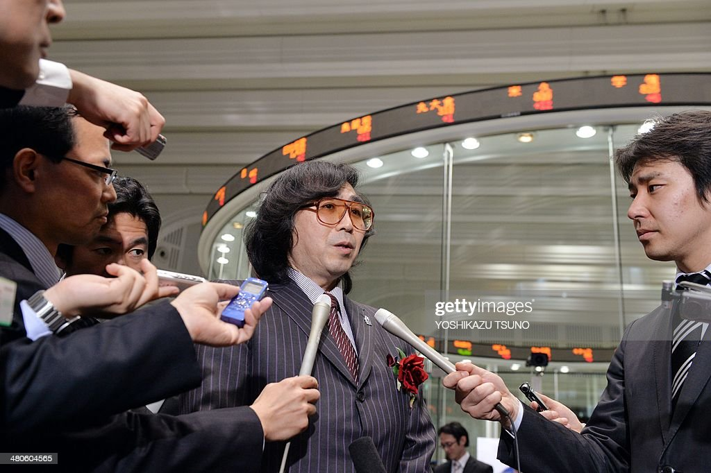 Yoshiyuki Sankai (C), University of Tsukuba professor and president of Japanese robot venture Cyberdyne, speaks to reporters as the company was listed at the Tokyo Stock Exchange's (TSE) Mothers market, aimed at providing venture companies access to funds at an early stage of their development at the TSE on March 26, 2014. Cyberdyne, the maker of a battery-powered exoskeleton robot suit, made its stock market debut, as the firm looks to raise money to boost its research. AFP PHOTO / Yoshikazu TSUNO