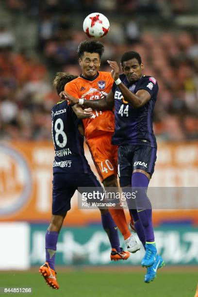 Yoshizumi Ogawa of Albirex Niigata competes for the ball against Yoshifumi Kashiwa and Anderson Lopes of Sanfrecce Hiroshima during the JLeague J1...