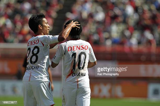 Yoshizumi Ogawa of Nagoya Grampus celebrates scoring his team's first goal with his teammate Taishi Taguchi during the JLeague match between Kashima...