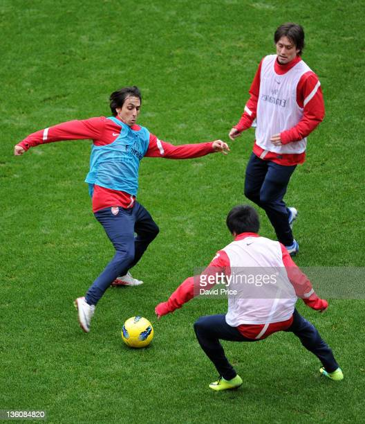 Yossi Benayoun is closed down by Tomas Rosicky and Ryo Miyaichi of Arsenal during a training session at the Emirates Stadium on December 23, 2011 in...