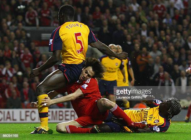 Yossi Benayoun of Liverpool tangles with Bacary Sagna and Kolo Toure of Arsenal as he scores his team's second goal during the Barclays Premier...