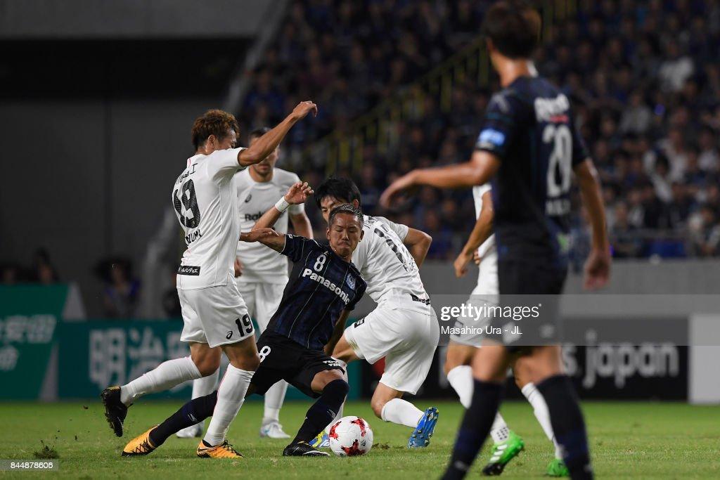 Yosuke Ideguchi of Gamba Osaka controls the ball under pressure of Vissel Kobe defense during the J.League J1 match between Gamba Osaka and Vissel Kobe at Suita City Football Stadium on September 9, 2017 in Suita, Osaka, Japan.