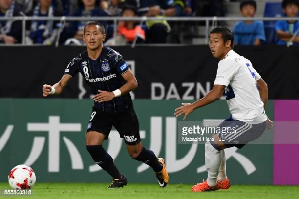 Yosuke Ideguchi of Gamba Osaka controls the ball under pressure of Takuya Kida of Yokohama FMarinos during the JLeague J1 match between Gamba Osaka...