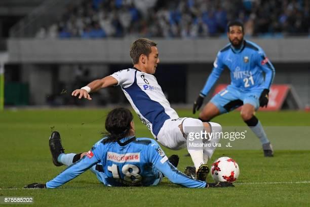 Yosuke Ideguchi of Gamba Osaka is tackled by Elsinho of Kawasaki Frontale during the JLeague J1 match between Kawasaki Frontale and Gamba Osaka at...