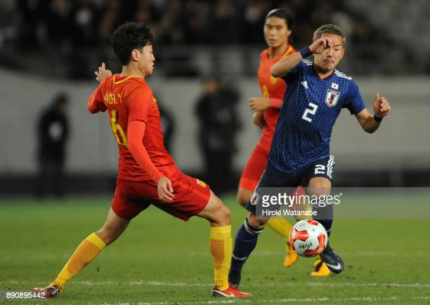 Yosuke Ideguchi of Japan anc Gao Zhunyi of China compete for the ball during the EAFF E1 Men's Football Championship between Japan and China at...