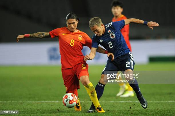 Yosuke Ideguchi of Japan and Zhao Yuhao of China compete for the ball during the EAFF E1 Men's Football Championship between Japan and China at...