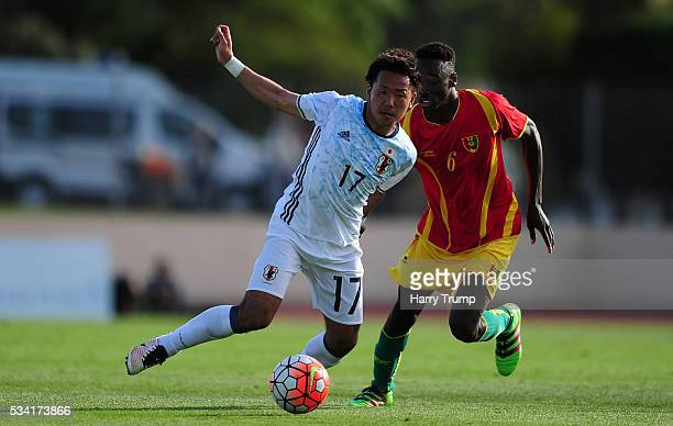Yosuke Ideguchi of Japan looks to break past Alpha Kaba of Guinea during the Toulon Tournament match between Guinea and Japan at Stade Antoinr...