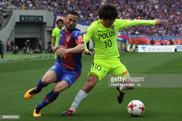 Yosuke Kashiwagi of Urawa Red Diamonds controls the ball under pressure of Takuma Abe of FC Tokyo during the J.League J1 match between FC Tokyo and...