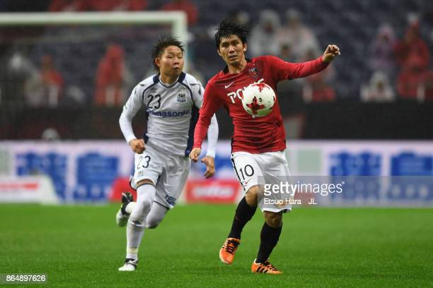 Yosuke Kashiwagi of Urawa Red Diamonds controls the ball under pressure of Shogo Nakahara of Gamba Osaka during the JLeague J1 match between Urawa...