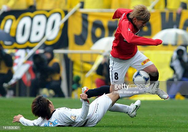 Yosuke Kashiwagi of Urawa Red Diamonds is tackled by Akimi Barata of Kashiwa Reysol during the JLeague match between Urawa Red Diamonds and Kashiwa...