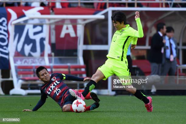 Yosuke Kashiwagi of Urawa Red Diamonds is tackled by Yasushi Endo of Kashima Antlers during the JLeague J1 match between Kashima Antlers and Urawa...