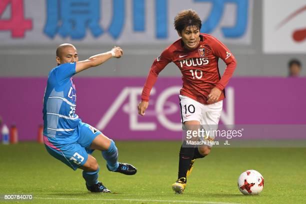 Yosuke Kashiwagi of Urawa Red Diamonds takes on Yutaka Yoshida of Sagan Tosu during the JLeague J1 match between Sagan Tosu and Urawa Red Diamonds at...