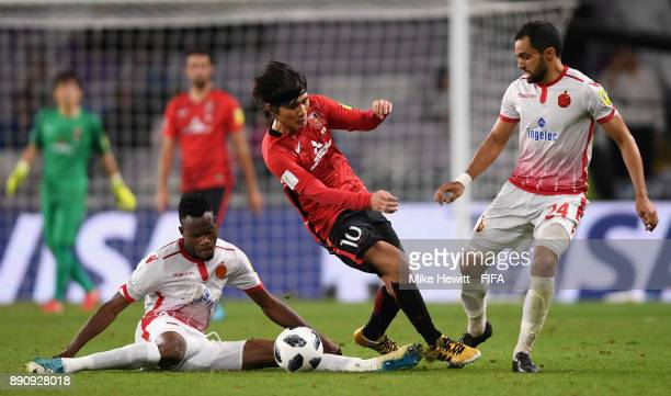 Yosuke Kashiwagi of Urawa Reds is tackled by Mouhamed Ouattara of Wydad Casablanca during the FIFA Club World Cup UAE 2017 fifth place playoff match...