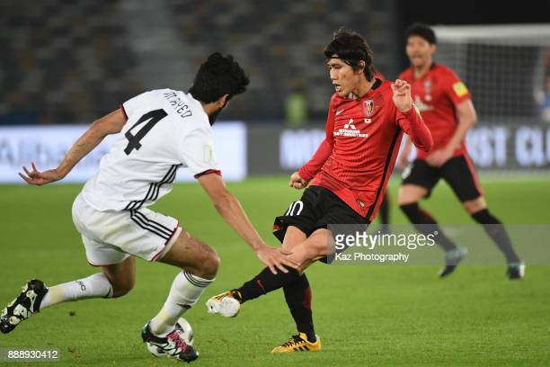 Yosuke Kashiwagi of Urawa Reds passes the ball under the pressure from Mohamed Ayed of Al Jazira on December 9 2017 in Abu Dhabi United Arab Emirates