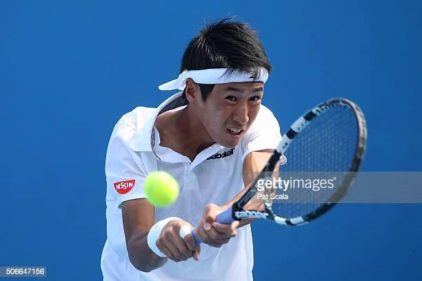 Yosuke Watanuki of Japan plays a backhand in his second round juniors match against Moerani Bouzige of Australia during the Australian Open 2016...