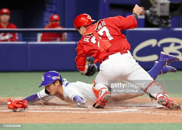 Yota Kyoda of the Chunichi Dragons slides safely into the home base to score a run by a RBI single of Zoilo Almonte in the 6th inning during the game...