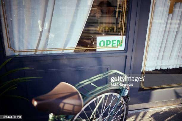 you can see the open sign hanging from the glass of the door. - store opening stock pictures, royalty-free photos & images