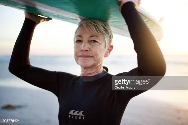 you never too old to go on surfing adventures - só uma mulher idosa imagens e fotografias de stock