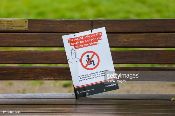 You should only use this bench for a short rest while exercising' poster on a north London park bench with a graffiti of an inappropriate drawing.