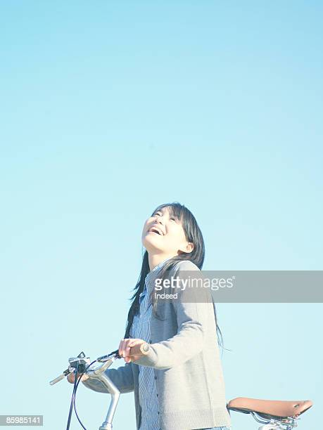 Yougn woman holding bicycle and looking at sky
