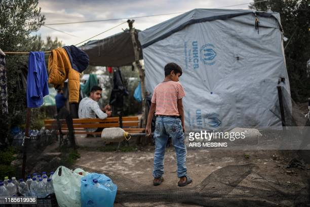 A yound boy lifts a handmade weight bar at a makeshift camp next to the camp of Moria on the Greek island of Lesbos on November 30 2019 Conditions...