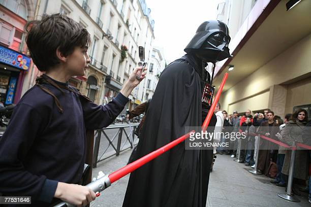 A yound boy takes a picture of a man disguised as character of US director George Lucas films Star Wars Dark Vador in front of the Grand Rex cinema...
