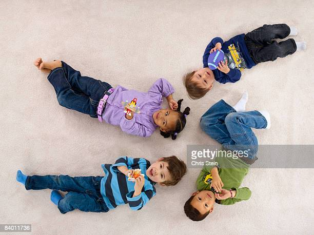 4 yound children playing on a carpet. - lying down stock pictures, royalty-free photos & images