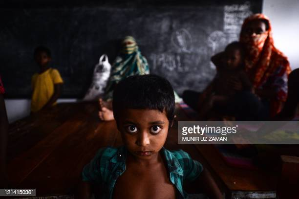 TOPSHOT A yound resident rests with others in a shelter ahead of the expected landfall of cyclone Amphan in Dacope of Khulna district on May 20 2020...